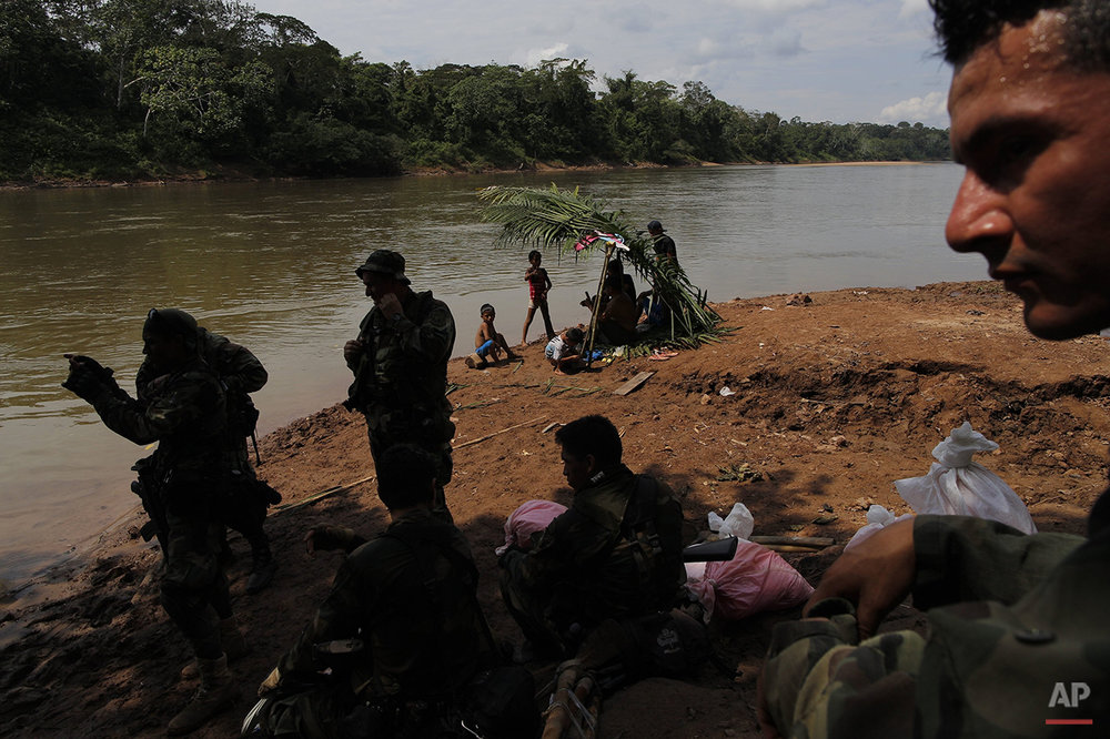 In this July 28, 2015 photo, a group of counternarcotics special forces wait for a boat to cross the Palcazu River as they head to crater a clandestine airstrip used by drug dealers near Ciudad Constitucion, Peru. On reaching the Palcazu River, they persuaded a boatman to motor them to the other side. (AP Photo/Rodrigo Abd)