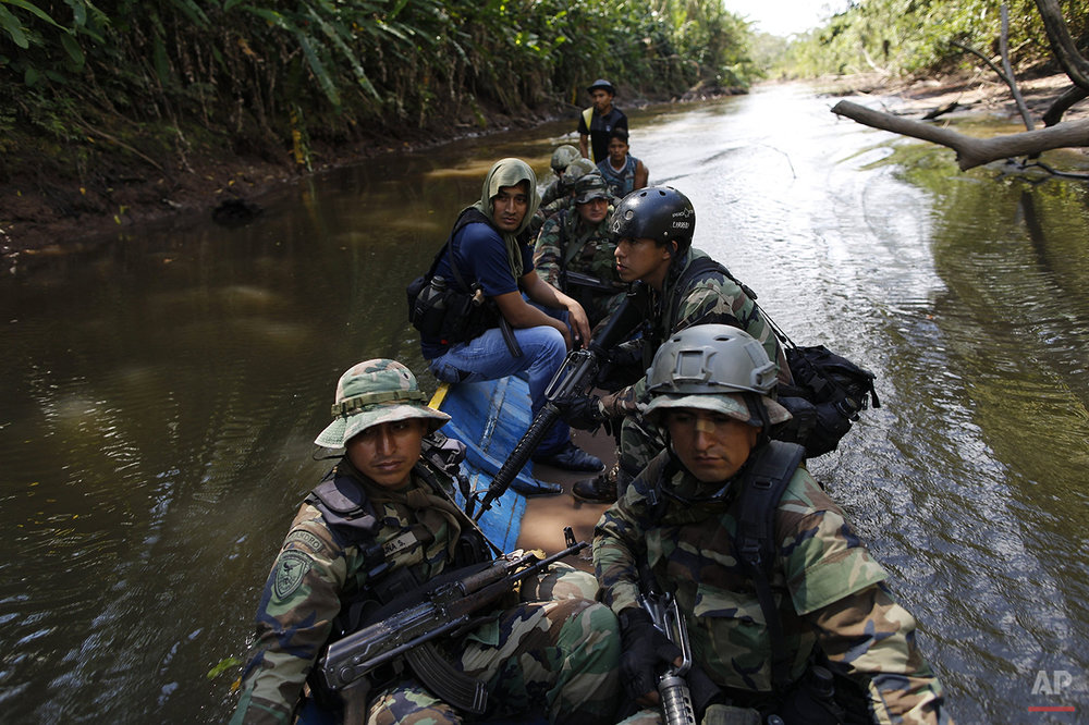 In this July 28, 2015 photo, counternarcotics special forces cross the Palcazu River as they head to crater a clandestine airstrip used by drug dealers in the Peruvian jungle near Ciudad Constitucion, Peru. The officers armed with assault rifles slowly negotiated rutted, muddy roads, walked for hours and forded streams to get to their destination. (AP Photo/Rodrigo Abd)