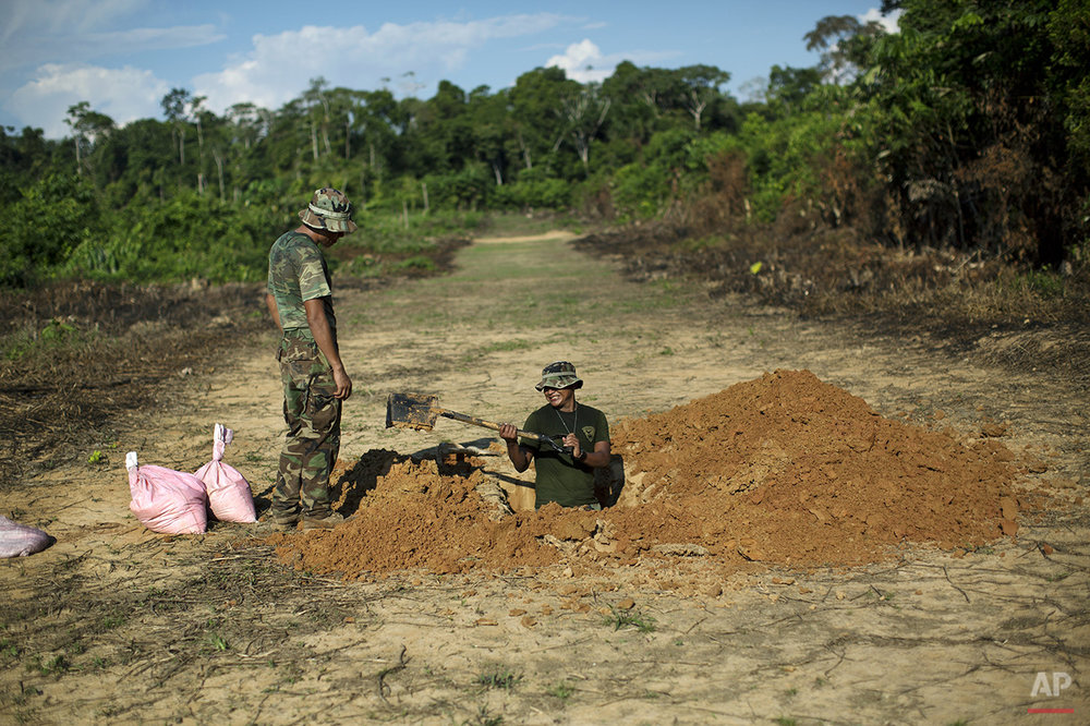 In this July 31, 2015 photo, counternarcotics special forces dig a ditch in a clandestine grassy airstrip used by drug traffickers in the jungle near Ciudad Constitucion, Peru. Explosives will be placed in the ditch to blow craters into the airstrip in an attempt to render it unusable. (AP Photo/Rodrigo Abd)