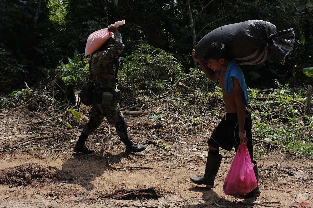 In this July 31, 2015 photo, a counternarcotics special forces officer carries a bag of ammonium nitrate explosives that will be used to crater a clandestine airstrip, as a local villager carries a sack filled with coca leaves near Ciudad Constitucion, Peru. The police regularly raid the pits in which coca leaves are processed into the paste used to make cocaine. (AP Photo/Rodrigo Abd)