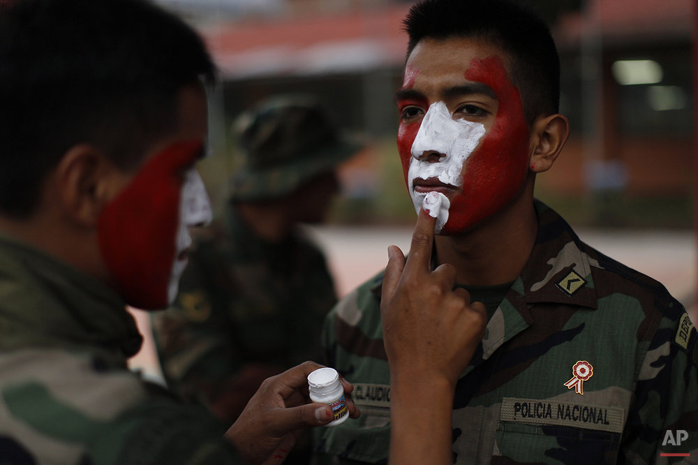In this July 27, 2015 photo, a counter narcotics police officer paints the face of a comrade before taking part in a parade commemorating Peru's Independence Day, inside their base in Tingo Maria, Peru. The men are part of the elite counternarcotics police who work in the dense central jungles of the world's No. 1 cocaine-producing nation. (AP Photo/Rodrigo Abd)
