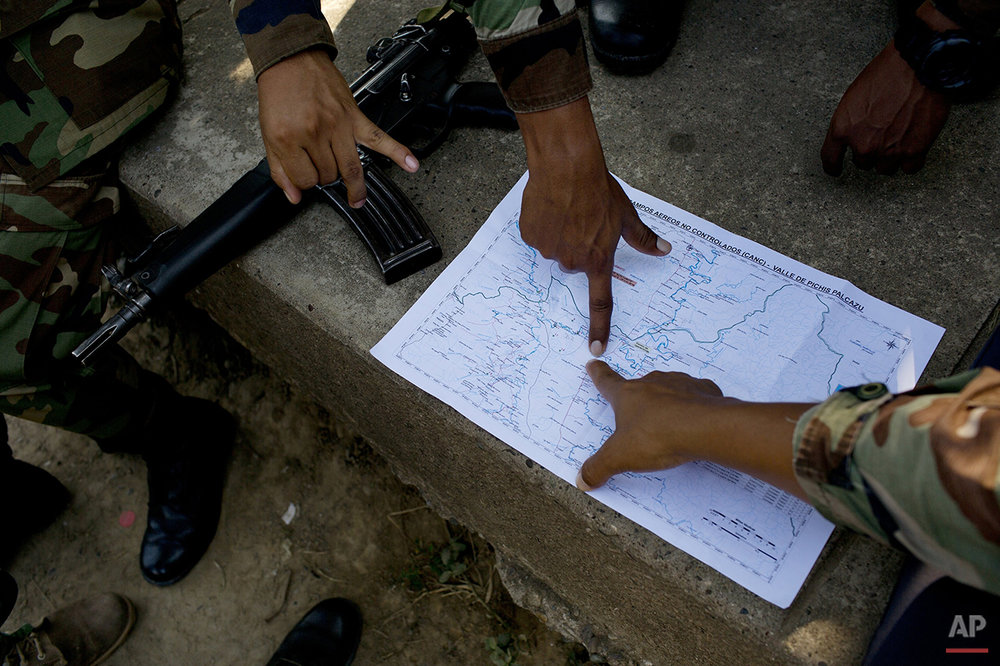In this July 31, 2015 photo, counternarcotics special forces study a map at their headquarters, before starting an operation to destroy a clandestine airstrip, in Ciudad Constitucion, Peru. According to Rep. Emiliano Apaza, president of Congress' defense committee, the Andean nation has been spending more than $8 million a year blasting holes in clandestine airstrips. (AP Photo/Rodrigo Abd)