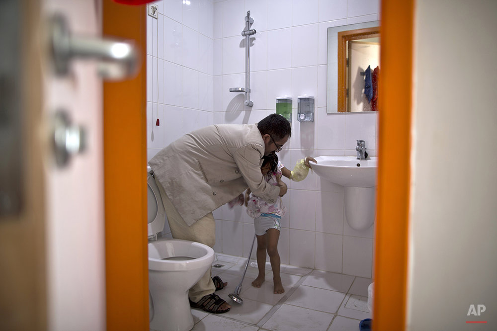In this Tuesday, Aug. 11, 2015 photo, Yemeni girl Najla Mohammed, 6, who was burnt in a fire at her home, is helped by her father to get dressed after showering her, in their room at MSF Hospital for Specialized Reconstructive Surgery, run by the international charity Médecins Sans Frontières (Doctors Without Borders) in Amman, Jordan.(AP Photo/Muhammed Muheisen)