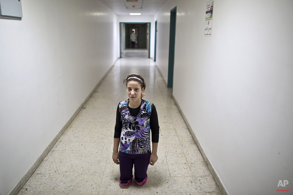 In this Tuesday, Aug. 11, 2015 photo, Syrian girl Salam Rashid, 14, who lost both of her legs below the knee in 2012 in a tank shell attack, poses for a picture at the MSF Hospital for Specialized Reconstructive Surgery in Amman, Jordan. The international charity Médecins Sans Frontières (Doctors Without Borders) officially inaugurates in Amman next month its new reconstructive surgery hospital for war victims, which it says is unique in the region. (AP Photo/Muhammed Muheisen)