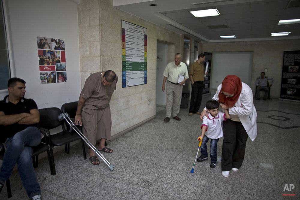 "In this Monday, Aug. 17, 2015 photo, Syrian child Mustafa Abdullah, 4, who suffered a broken hip in 2014 in an airstrike that killed his parents, is helped by a doctor at MSF Hospital for Specialized Reconstructive Surgery, run by the international charity Médecins Sans Frontières (Doctors Without Borders) in Amman, Jordan. He has been undergoing intense physiotherapy at the hospital, trying to graduate from a tiny walker to crutches. ""The whole hospital loves him,"" says his grandmother Fadila, who cares for him. (AP Photo/Muhammed Muheisen)"