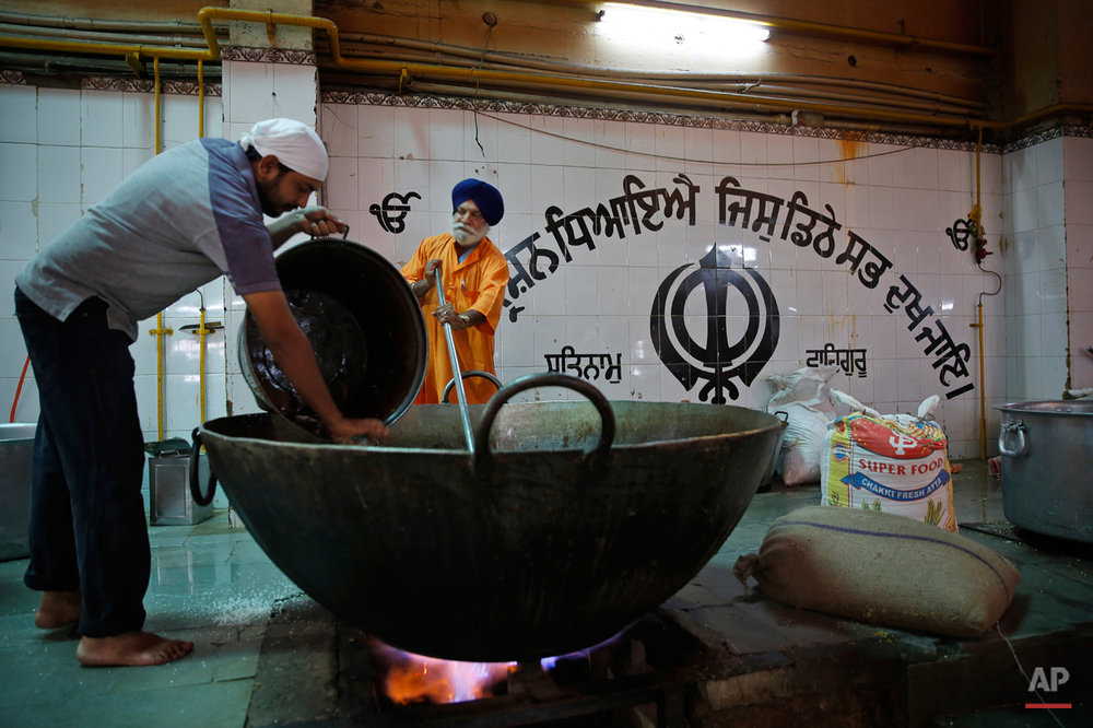 In this June 3, 2015, photo, Sikh devotees prepare langar, which translates to community dinner, at Bangla Sahib Gurudwara or Sikh temple, in New Delhi, India. Men, women and children throng the kitchen at Bangla Sahib, one of the biggest gurudwaras in India, that feeds more than 10,000 people every day. It is now a tradition followed by more than 30 million Sikhs worldwide. Nearly every Gurdwara in the world, irrespective of size, has a kitchen and serves langar. (AP Photo/Manish Swarup)