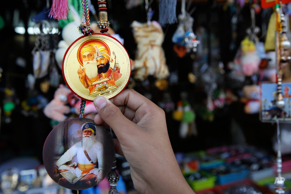 In this June 3, 2015 photo, a devotee holds a badge with portraits of Guru Nanak, left, who founded Sikhism in late 15th century, and Guru Gobind Singh, after eating langar, which translates to community dinner, at Bangla Sahib Gurudwara or Sikh temple in New Delhi, India. Men, women and children throng the kitchen at Bangla Sahib, one of the biggest gurudwara in India, that serves langar, the community meal, served to more than 10,000 people every day. It is now a tradition followed by more than 30 million Sikhs worldwide. Nearly every Gurdwara in the world, irrespective of sizes, has a kitchen and serves langar. (AP Photo/Manish Swarup)
