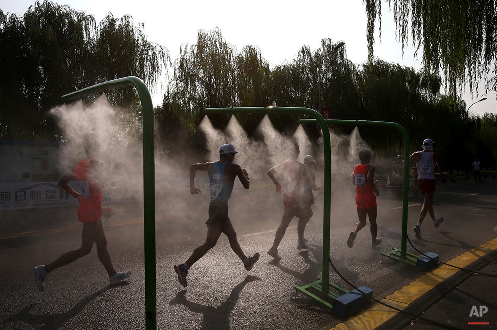 Competitors go through a cooling mist during the men's 50k race walk at the World Athletics Championships outside the Bird's Nest stadium in Beijing, Saturday, Aug. 29, 2015. (AP Photo/Kin Cheung)