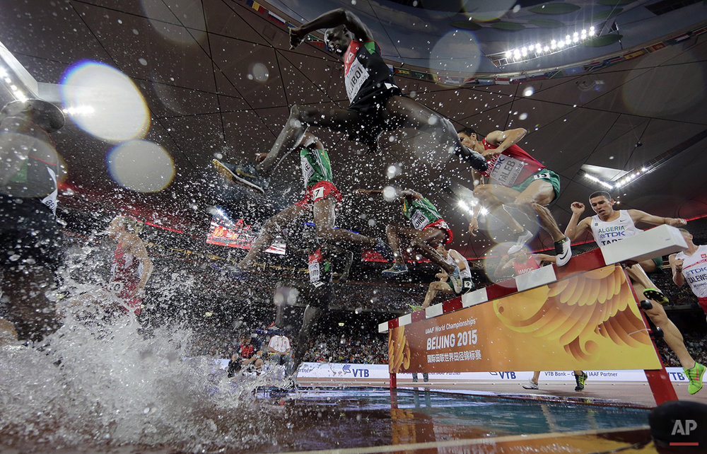 Kenya's Ezekiel Kemboi, centre, takes the water jump on his way to winning the gold medal in the men's 3000m steeplechase final at the World Athletics Championships at the Bird's Nest stadium in Beijing, Monday, Aug. 24, 2015. (AP Photo/Andy Wong)