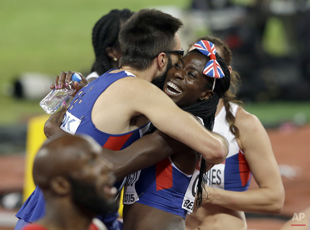 Martyn Rooney and Britain's Christine Ohuruogu of the British men's and women's 4x400m relay teams embrace after both won bronze medals at the World Athletics Championships at the Bird's Nest stadium in Beijing, Sunday, Aug. 30, 2015. (AP Photo/Darron Cummings)