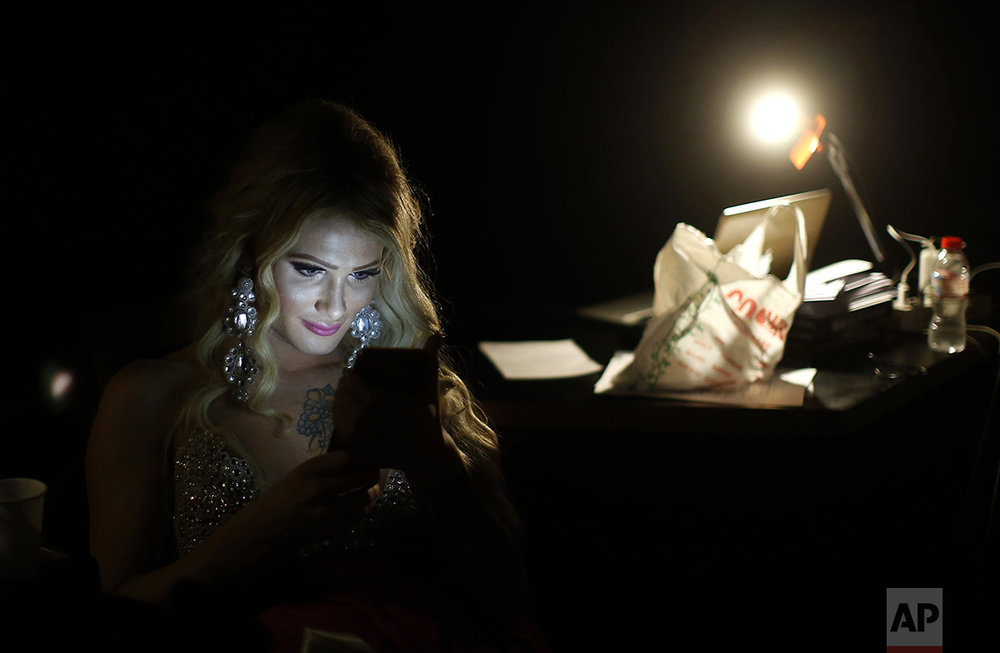 In this Sunday, Sept. 18, 2016 photo, Paris Nemc from Slovakia, looks at her phone during an interval at Miss Trans Star International 2016 show celebrated in Barcelona, Spain. Twenty-eight women representing as many countries competed last weekend to be crowned  Miss Trans Star International, Europe's largest beauty pageant for transgender women and one of a growing number of similar events aimed at celebrating a population more often condemned. (AP Photo/Manu Fernandez)