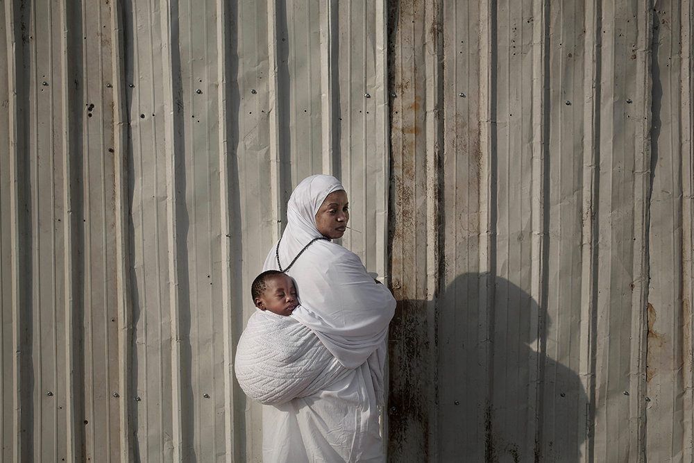In this Sunday, Sept. 11, 2016 photo, Fatma, 25, from Ghana carries her son Hisou as she poses for a photograph in Arafat during the annual hajj pilgrimage, near the holy city of Mecca, Saudi Arabia. Fatma walked with her son from Madina to Mecca to Arafat and will complete her pilgrimage by walking and not using any vehicles. (AP Photo/Nariman El-Mofty)