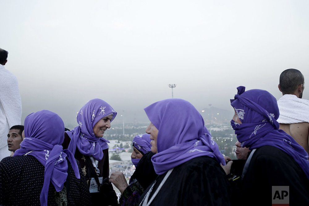 In this Sunday, Sept. 11, 2016 photo, Syrian women from Hama make their way down after prayer on a rocky hill known as the Mountain of Mercy, on the Plain of Arafat, during the annual hajj pilgrimage, near the holy city of Mecca, Saudi Arabia. (AP Photo/Nariman El-Mofty)
