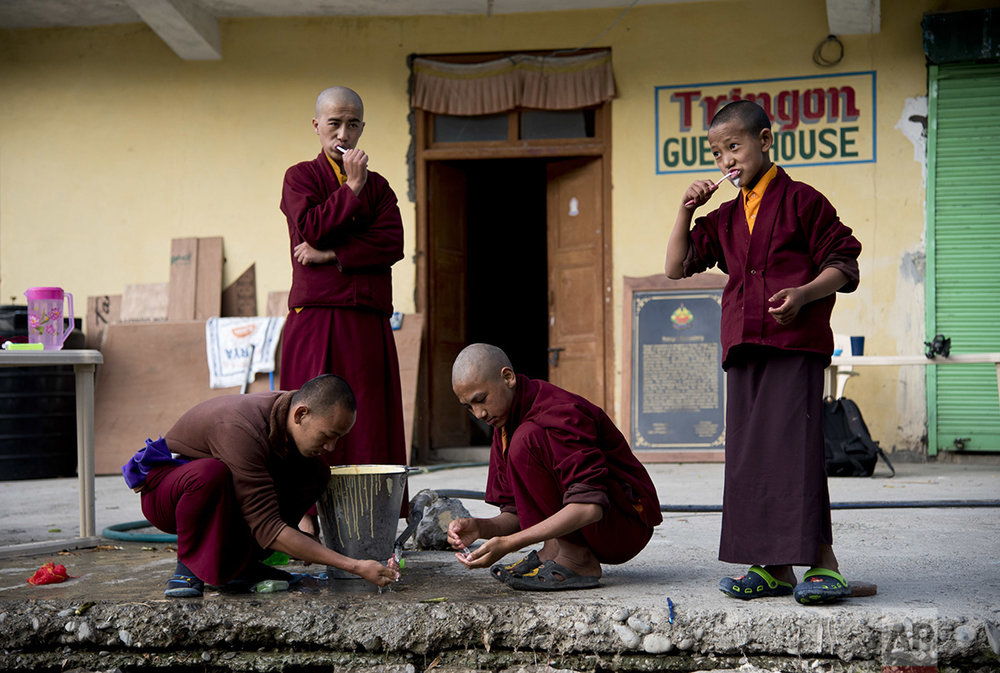 In this Aug. 20, 2016, photo, a group of young monks brush their teeth at the Kongri monastery, Spiti Valley, India. For centuries, the sleepy valley nestled in the Indian Himalayas remained a hidden Buddhist enclave forbidden to outsiders. That's all now starting to change since India began allowing its own citizens as well as outsiders to visit the valley in the early 1990s. Some villagers and travelers worry the influx of new funds will bring competition, greed and environmentally taxing change, such as flush toilets that might empty straight into the Spiti River, or a strain on the region's already limited water sources. (AP Photo/Thomas Cytrynowicz)