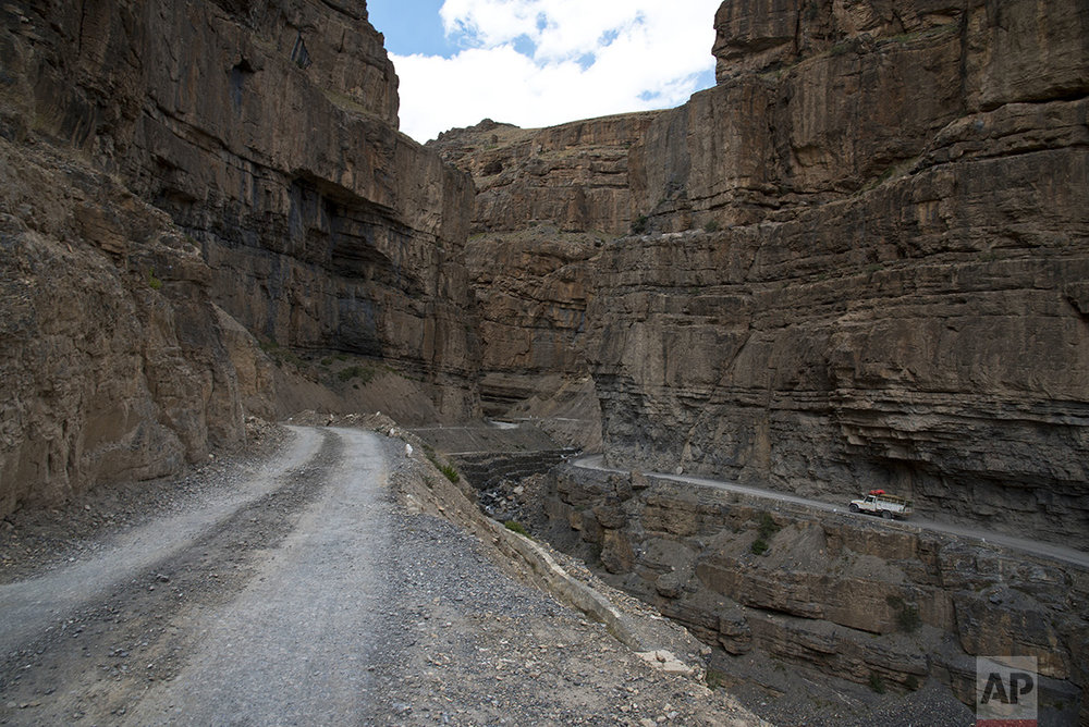 In this Aug. 15, 2016, photo, a car drives along a mountain road that leads to Spiti Valley, a remote Himalayan valley situated at 4000 meter above sea level, India. (AP Photo/Thomas Cytrynowicz)