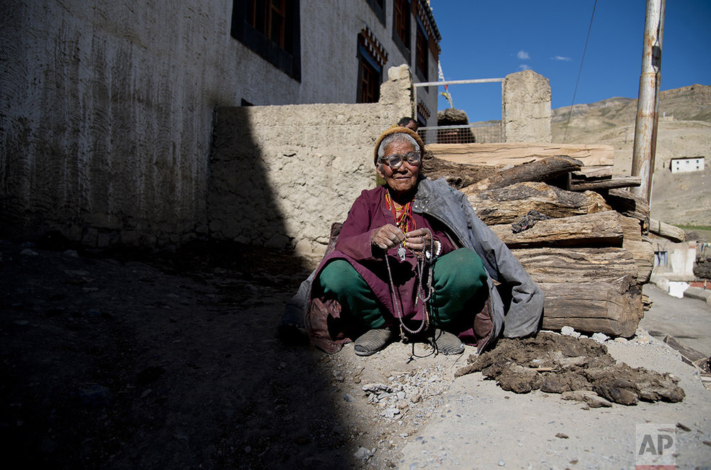 In this Aug. 16, 2016, photo, an elderly woman sits in front of her house in the village of Kibber, in Spiti Valley, India. (AP Photo/Thomas Cytrynowicz)
