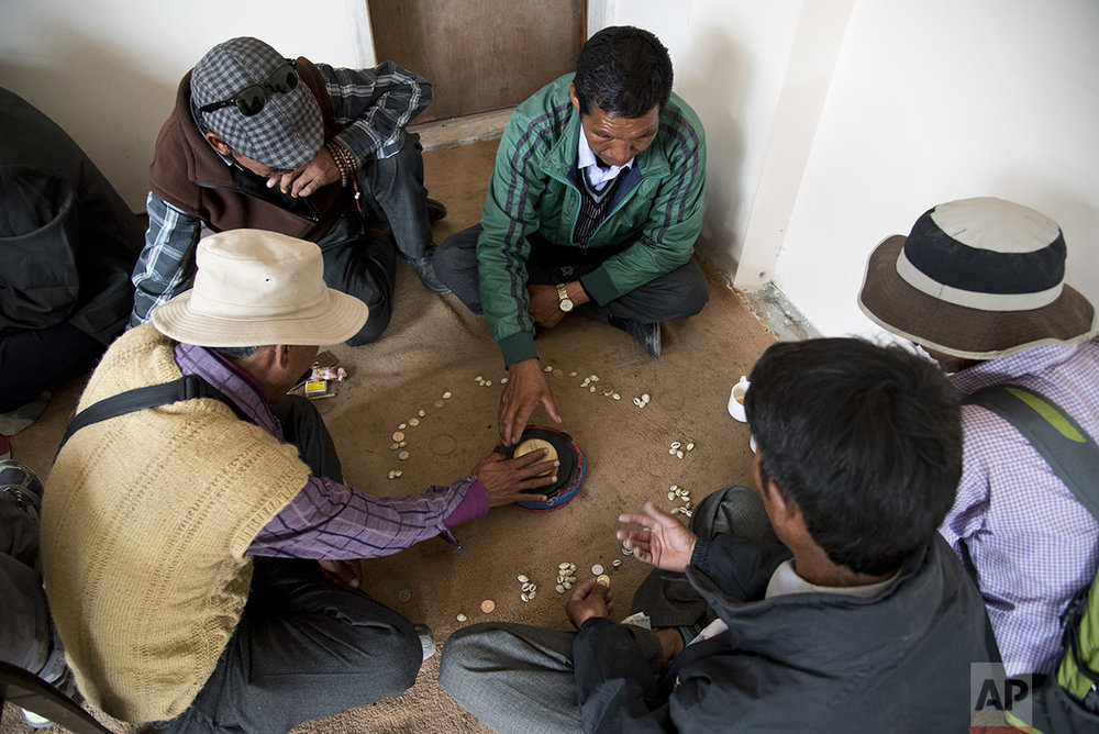 In this Aug. 20, 2016 photo, elders play 'chollo', a game where they shout as they throw the dice to bring good luck, in the city of Kaza, Spiti Valley, India. (AP Photo/Thomas Cytrynowicz)