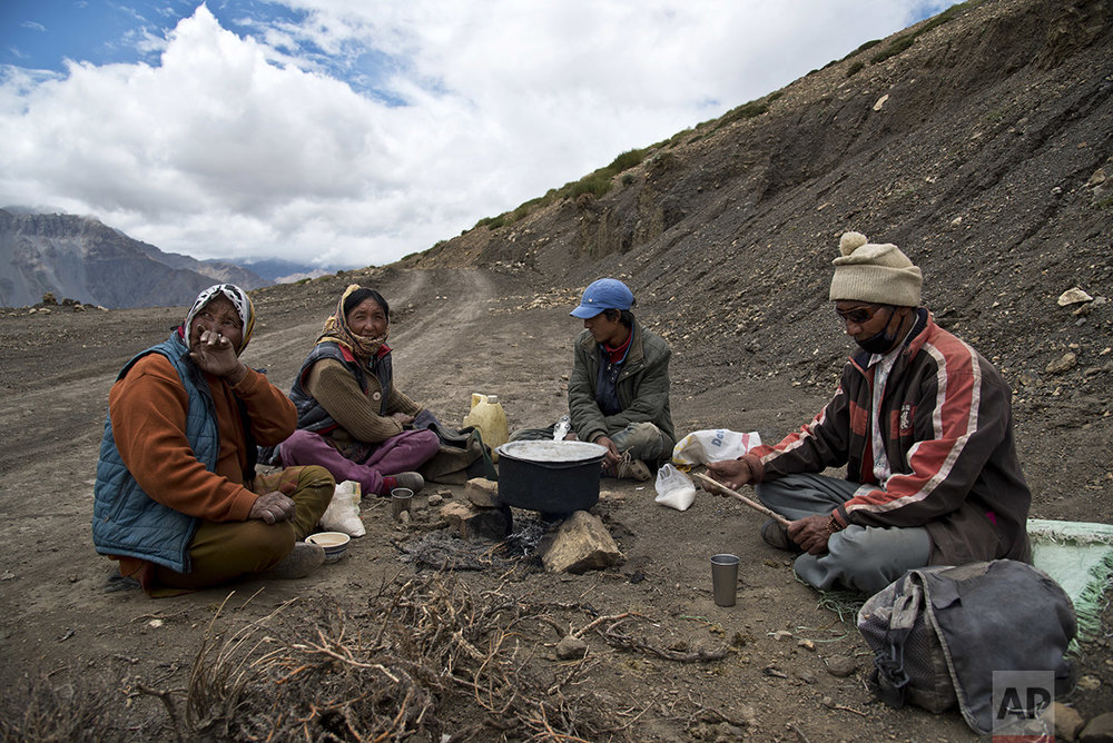 In this Aug. 17, 2016, photo, from left to right, Chhering Chodom, 60, Tashi Yangzom, 50, Lobsang Chhering, 27, and Dorje Tandup, 58, drink milk tea on the side of the road. (AP Photo/Thomas Cytrynowicz)