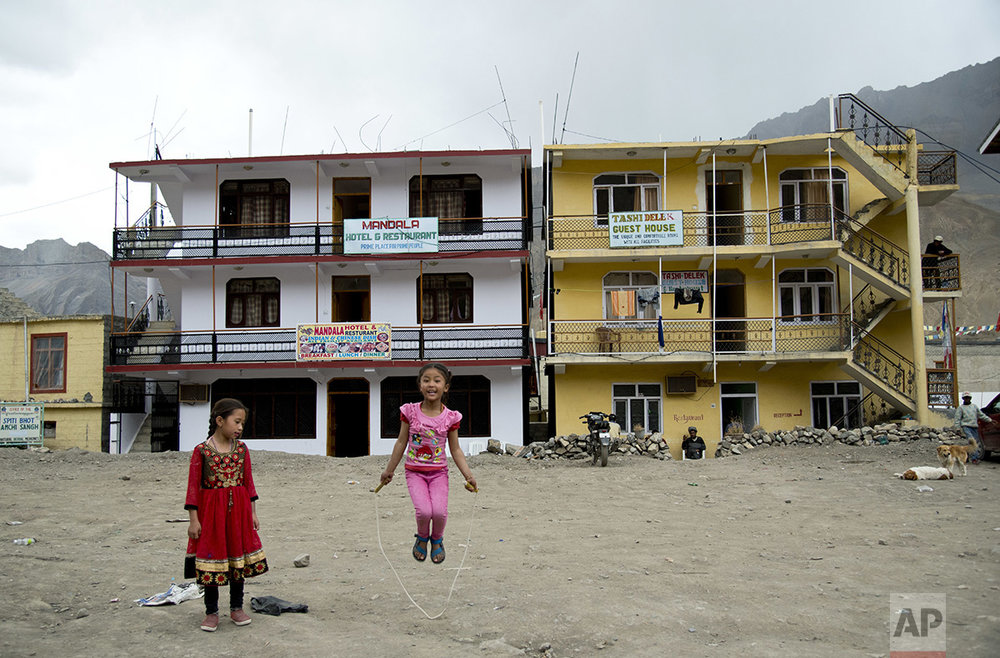 In this Aug. 20, 2016, photo, two girls play in front of newly constructed hotels in Kaza, headquarters of the Spiti Valley, India. (AP Photo/Thomas Cytrynowicz)