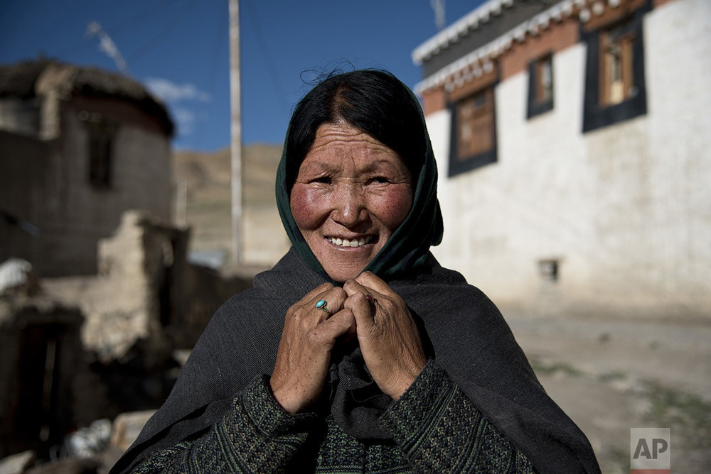 In this Aug. 16, 2016, photo, a woman ties a scarf around her head to protect herself from the wind in the village of Kibber, in Spiti Valley, India. (AP Photo/Thomas Cytrynowicz)