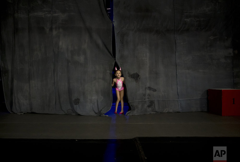 In this Sept. 10, 2016 picture, Diana Romaniuc, 7 years-old, peers from behind curtains before competing in the children category of the Romania Miss Pole Dance  Contest, ahead of the finals of the Pole Sport&Fitness World Championship  2016 in Bucharest, Romania. (AP Photo/Vadim Ghirda)