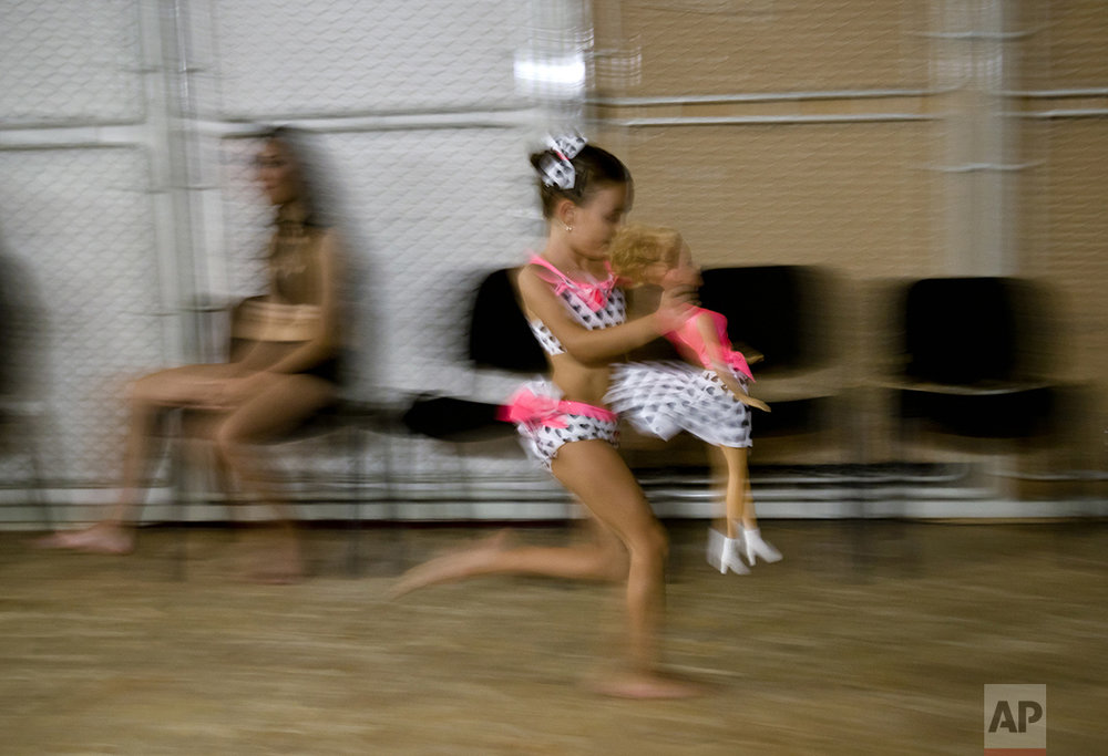 In this Sept. 10, 2016 picture, Denisa Maria Preda, 6 years-old, runs holding a doll, before competing in the children category of the Romania Miss Pole Dance Contest, ahead of the finals of the Pole Sport & Fitness World Championship 2016 in Bucharest, Romania. Contestants from 12 countries, including China, Russia. (AP Photo/Vadim Ghirda)
