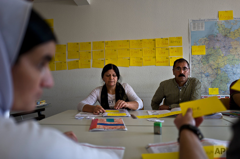 In this Wednesday, Sept. 14, 2016 photo, Samir Qasu, 46, right, and his wife Bessi Qasim, 43, Yazidi migrants from Sinjar, Iraq, attend their integration course at the town hall in Denzlingen, Germany. (AP Photo/Muhammed Muheisen)