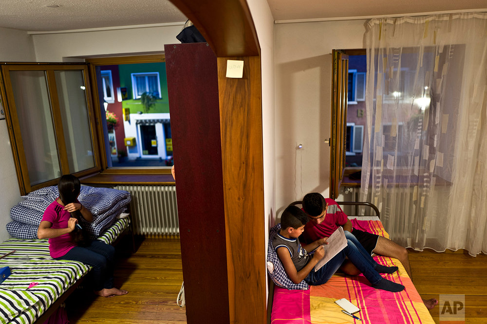 In this Wednesday, Sept. 14, 2016 photo, Dunia Qasu, 14, left, sits on her bed combing her hair while her elder brother Dilshad, 18, helps his younger brother Dildar, 11, in his homework, at their apartment in Elzach, Germany. (AP Photo/Muhammed Muheisen)