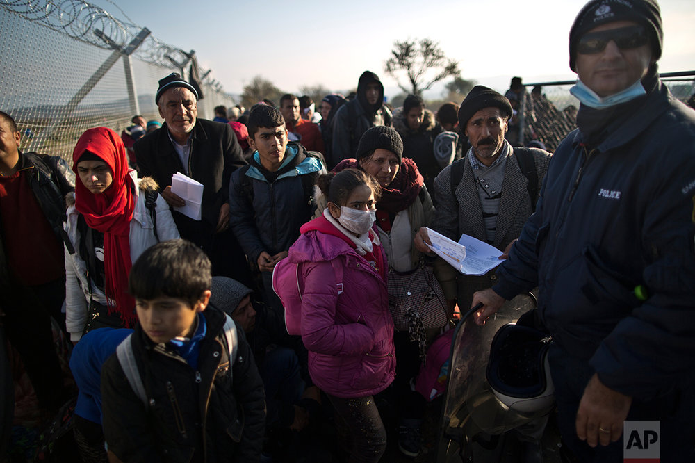 In this Saturday, Dec. 5, 2015 photo, Yazidi refugee Samir Qasu, 45, right, from Sinjar, Iraq, and his wife Bessi, 42, sons Dilshad, 17, Dildar, 10, and daughter Dunia, 13, stand behind a Greek police officer waiting to be permitted to cross the Greek-Macedonian border, near the northern Greek village of Idomeni. (AP Photo/Muhammed Muheisen)