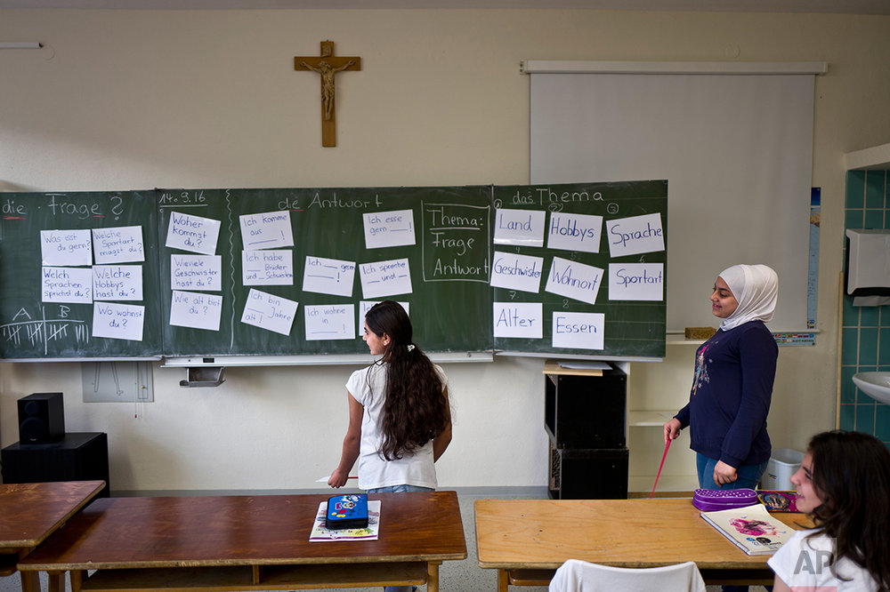In this Thursday, Sept. 15, 2016 photo, Dunia  Qasu, 14, center, a Yazidi migrant from Sinjar, Iraq, attends a German language class at her school, Schulzentrum Oberes Elztal, in Oberwinden, Germany. (AP Photo/Muhammed Muheisen)