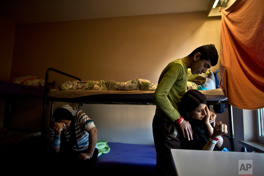In this Thursday, Dec. 10, 2015 photo, Delphine Qasu, 18, right, a Yazidi refugee from Sinjar, Iraq, is comforted by her brother Dilshad, 17, while crying after talking about their journey to reach Germany, at their new temporary home at Patrick Henry Village, in Heidelberg, Germany. (AP Photo/Muhammed Muheisen)