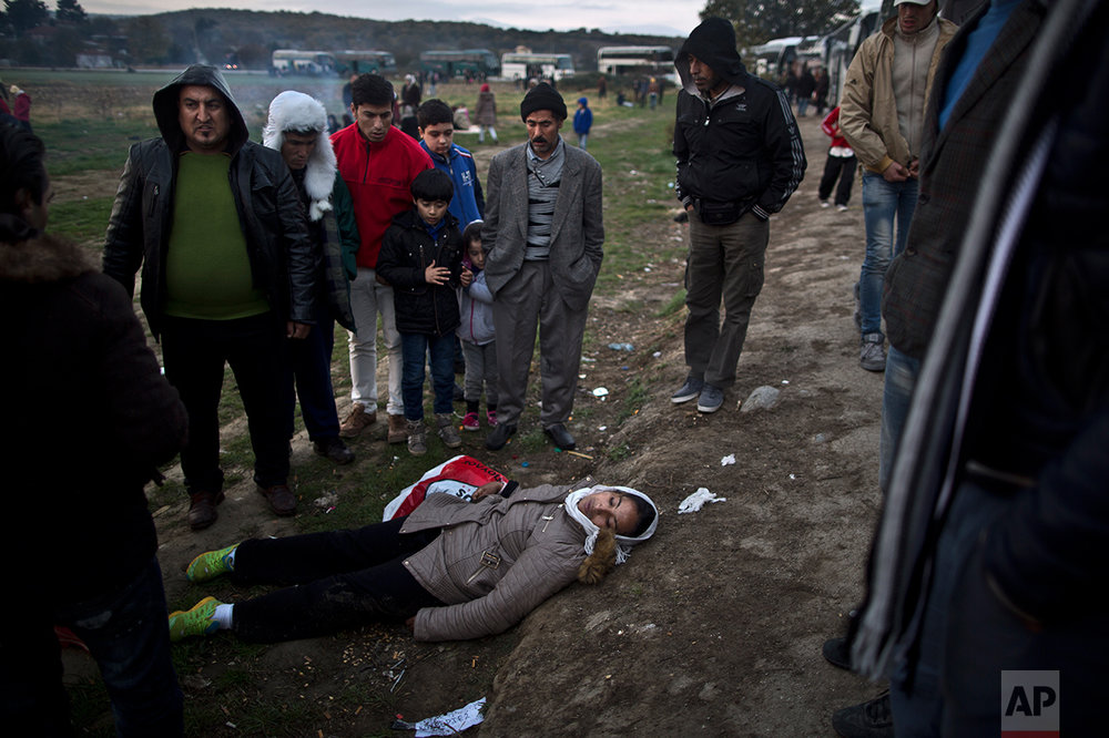 In this Saturday, Dec. 5, 2015 photo, Yazidi refugee Samir Qasu, 45, center, from Sinjar, Iraq, and his son Dildar, 10, stand with other refugees from Syria and Afghanistan around a Syrian refugee woman who collapsed while waiting to be permitted by Greek police to cross the Greek-Macedonian border, near the northern Greek village of Idomeni. (AP Photo/Muhammed Muheisen)
