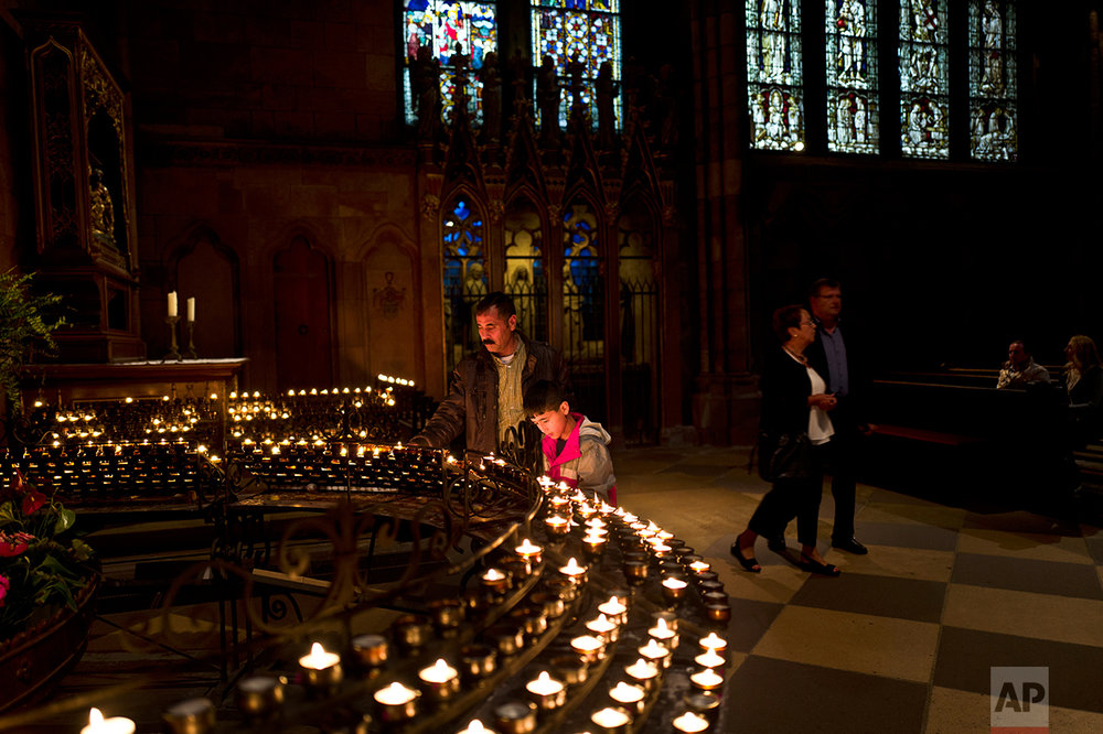 In this Friday, Sept. 16, 2016 photo, Samir Qasu, 46, and his son Dildar, 11, light candles while visiting Freiburg Minster in Freiburg, Germany. (AP Photo/Muhammed Muheisen)