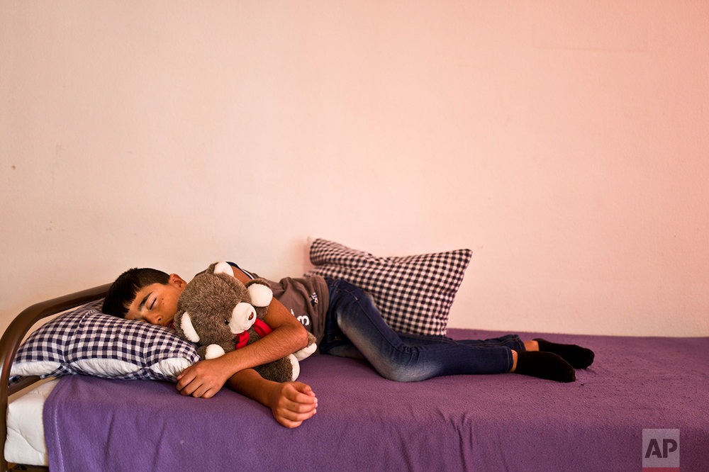 In this Friday, Sept. 16, 2016 photo, Dildar Qasu, 11, a Yazidi migrant from Sinjar, Iraq, sleeps on his sister's bed after coming back from school at his family's apartment in Elzach, Germany. (AP Photo/Muhammed Muheisen)