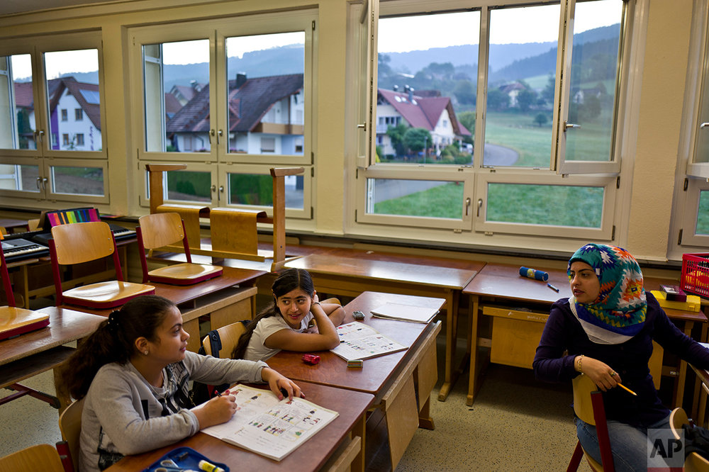 In this Thursday, Sept. 15, 2016 photo, Dunia  Qasu, 14, center, a Yazidi migrant from Sinjar, Iraq, talks with other classmates from Syria, during a German language class at her school, Schulzentrum Oberes Elztal, in Oberwinden, Germany. (AP Photo/Muhammed Muheisen)