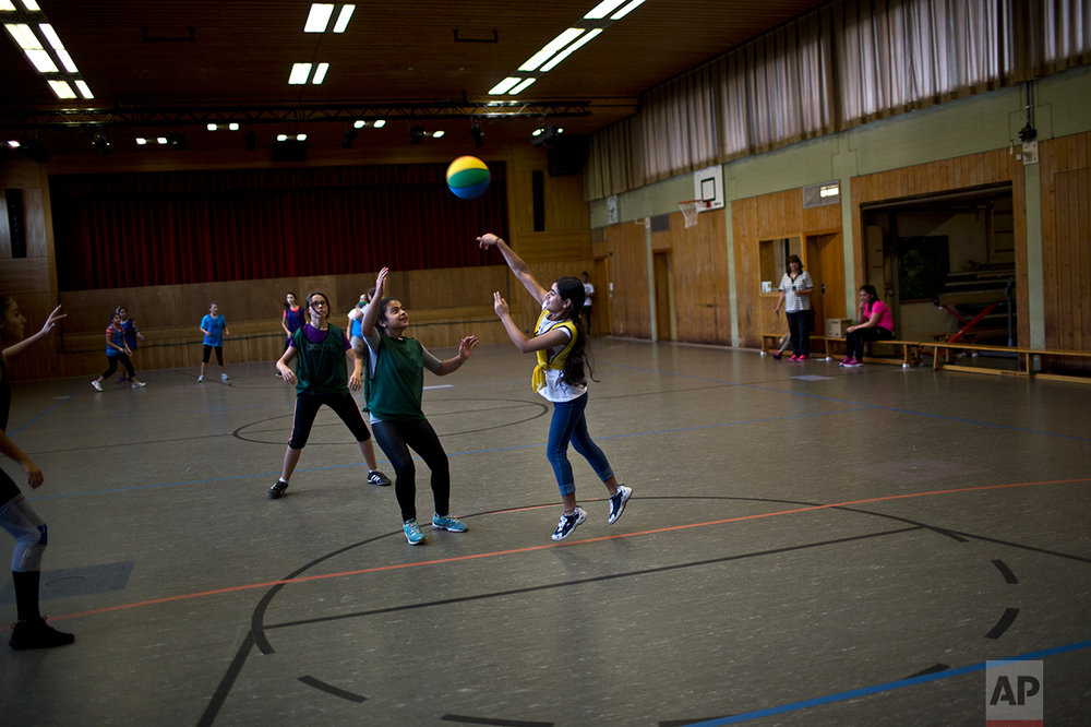 In this Thursday, Sept. 15, 2016 photo, Dunia  Qasu, 14, center, a Yazidi migrant from Sinjar, Iraq, throws the ball while she and her classmates practice basketball during a sport class at her school, Schulzentrum Oberes Elztal, in Oberwinden, Germany. (AP Photo/Muhammed Muheisen)