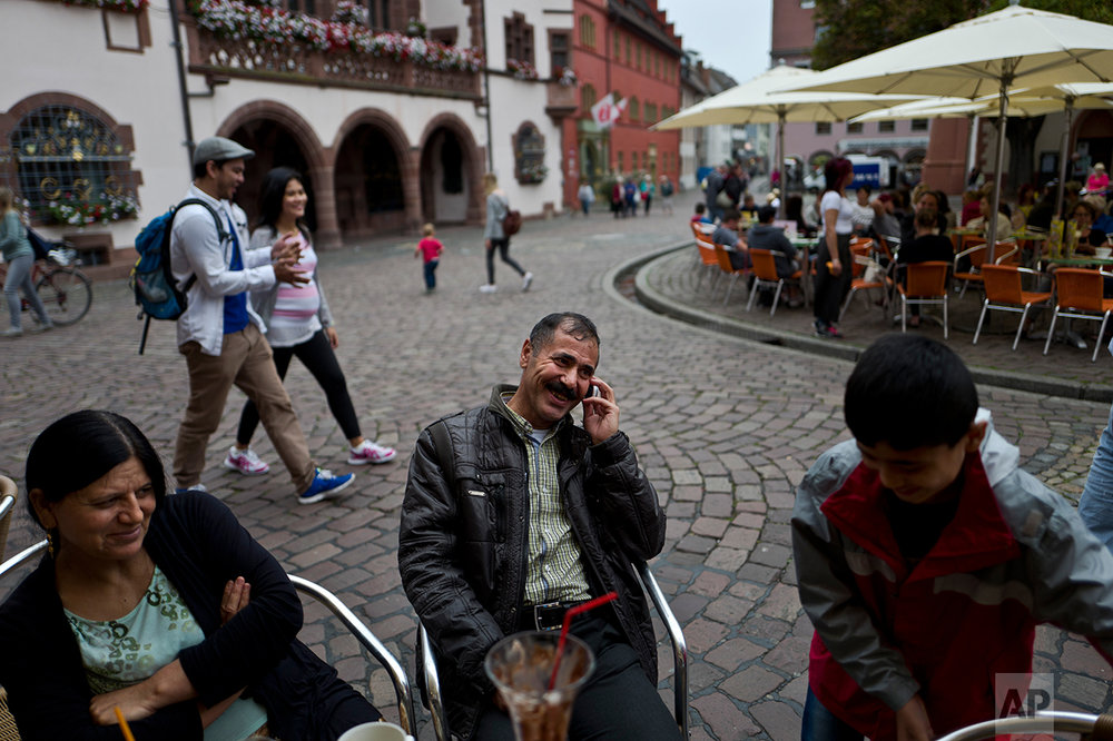 In this Friday, Sept. 16, 2016 photo, Samir Qasu, 46, center, a Yazidi migrant from Sinjar, Iraq, laughs while speaking on his mobile phone as he and his wife Bessi Qasim, 43, left, and his son Dildar Qasu, 11, enjoy their time at a cafe in Freiburg, Germany. (AP Photo/Muhammed Muheisen)