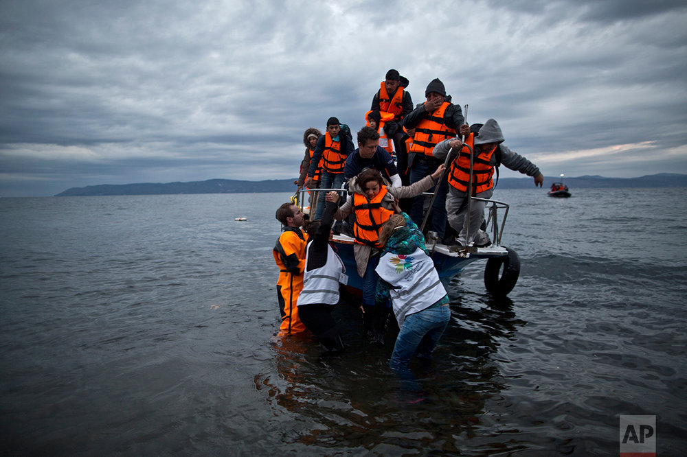 In this Thursday, Dec. 3, 2015 photo, volunteers help refugees disembark from a vessel carrying Yazidi refugee Samir Qasu, 45, from Sinjar, Iraq, and his wife Bessi, 42, their two daughters Delphine, 18, seen center left,  Dunia 13, and their two sons Dilshad, 17, seen center left, and Dildar, 10, as it arrives to the northeastern Greek island of Lesbos from the Turkish coast. (AP Photo/Muhammed Muheisen)