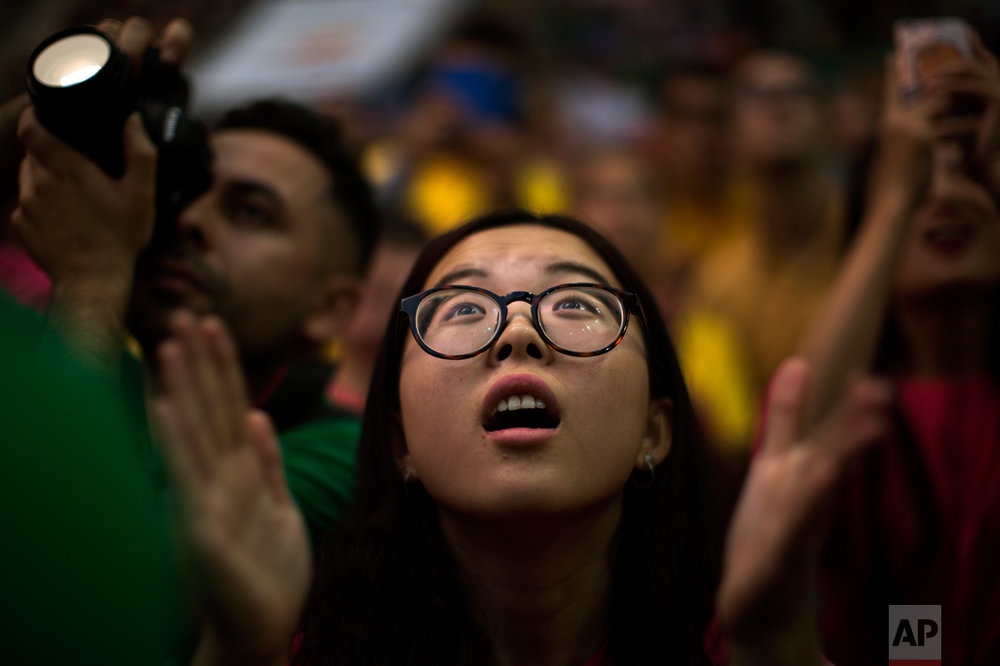 In this Saturday, Oct. 1, 2016 photo, Xiaotong Feng, 24, from China, reacts as she looks at members of Xiquets de Hangzou trying to complete their human tower, during the 26th Human Tower Competition in Tarragona, Spain. (AP Photo/Emilio Morenatti)