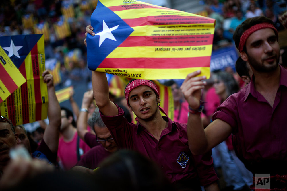 """Members of the """"Colla Jove de Sitges"""" hold independence flags and shout slogans during the 26th Human Tower Competition in Tarragona, Spain, on Saturday, Oct. 1, 2016. (AP Photo/Emilio Morenatti)"""