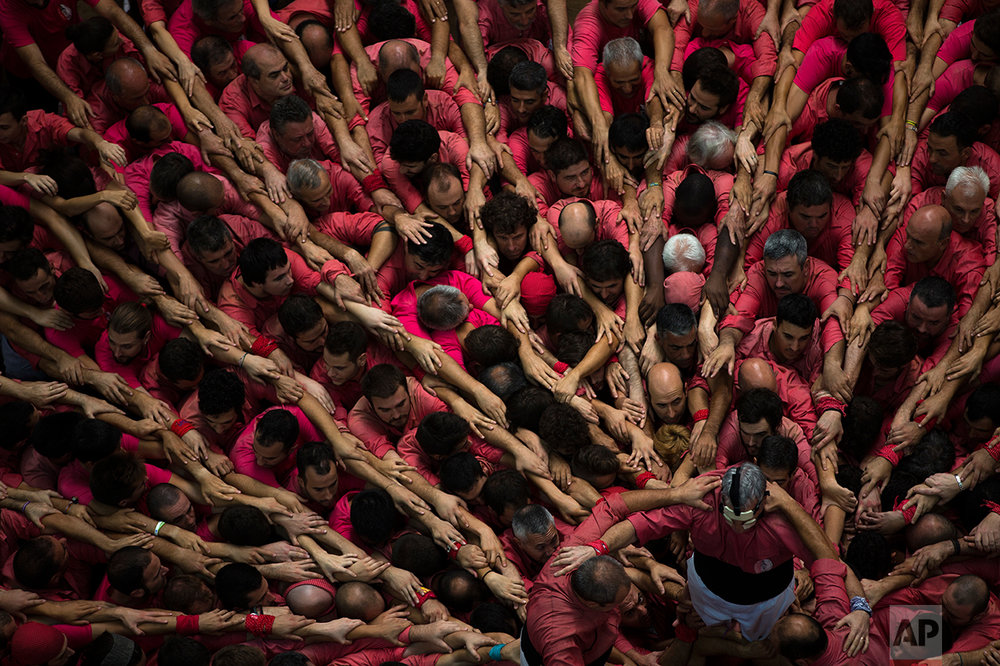 """Members of """"Vella de Xiquets de Valls"""" form their human tower during the 26th Human Tower Competition in Tarragona, Spain, on Sunday, Oct. 2, 2016. (AP Photo/Emilio Morenatti)"""