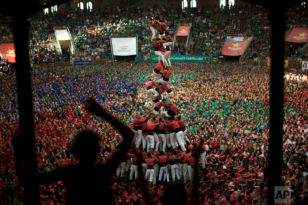 """Members of """"Vella de Xiquets de Valls"""" fall as they try to complete their human tower during the 26th Human Tower Competition in Tarragona, Spain, on Sunday, Oct. 2, 2016. (AP Photo/Emilio Morenatti)"""
