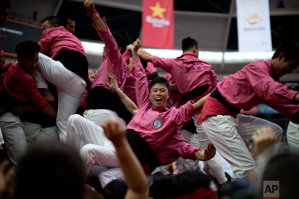 In this Saturday, Oct. 1, 2016 photo, members of Xiquets de Hangzou celebrate after completing their human tower, during the 26th Human Tower Competition in Tarragona, Spain. (AP Photo/Emilio Morenatti)