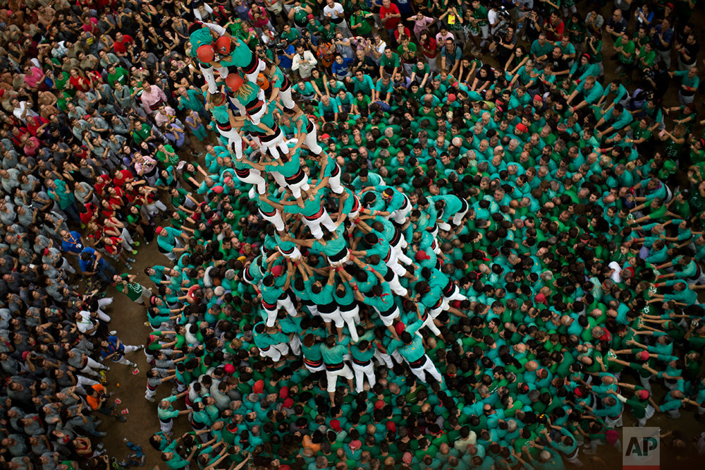 """Members of the """"Castellers de Villafranca"""" try to complete their human tower during the 26th Human Tower Competition in Tarragona, Spain, on Sunday, Oct. 2, 2016. (AP Photo/Emilio Morenatti)"""