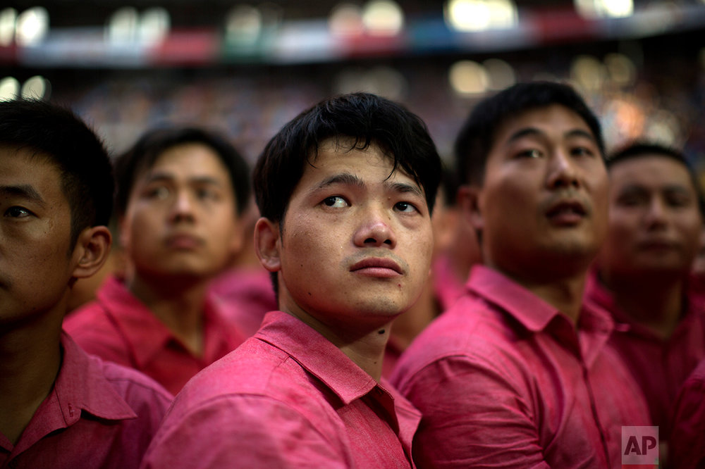 In this Saturday, Oct. 1, 2016 photo, members of Xiquets de Hangzou look at other castellers completing their human tower, during the 26th Human Tower Competition in Tarragona, Spain. (AP Photo/Emilio Morenatti)