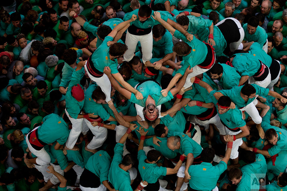 """Members of the """"Castellers de Villafranca"""" react after completing their human tower during the 26th Human Tower Competition in Tarragona, Spain, on Sunday, Oct. 2, 2016. (AP Photo/Emilio Morenatti)"""