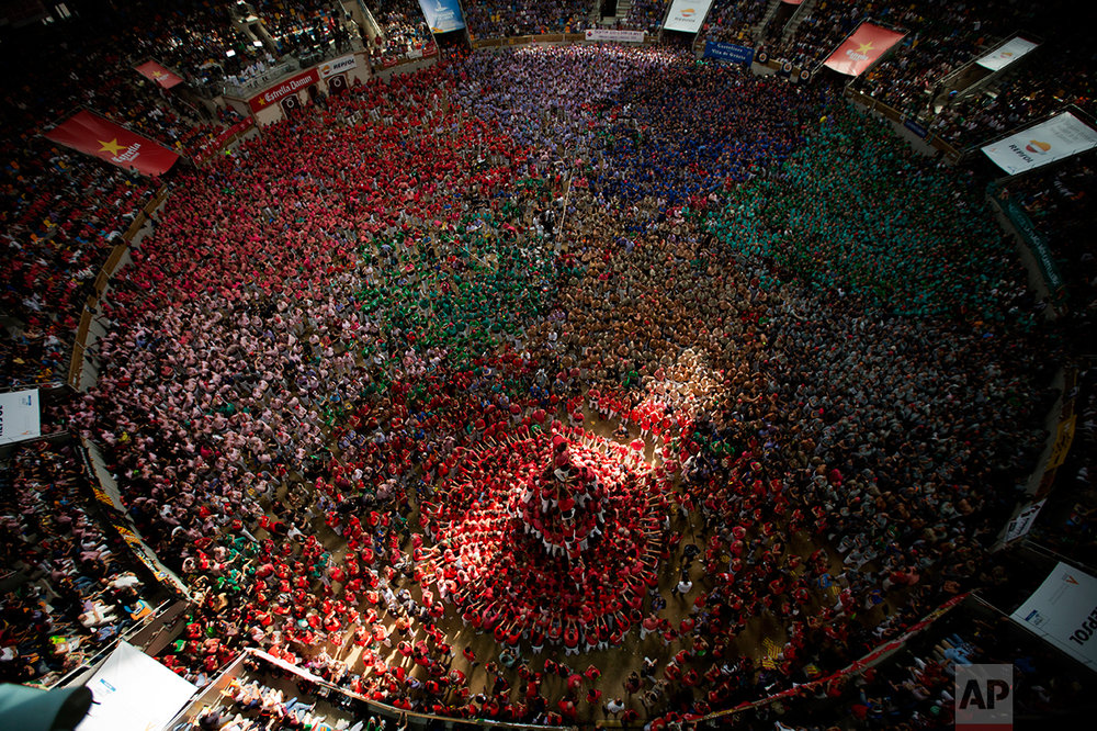 """Members of """"Vella de Xiquets de Valls"""" try to complete their human tower during the 26th Human Tower Competition in Tarragona, Spain, on Sunday, Oct. 2, 2016. (AP Photo/Emilio Morenatti)"""