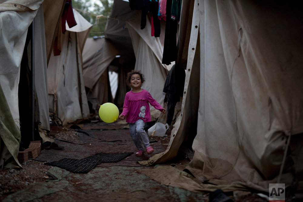 In this Thursday, Sept. 22, 2016 photo, a Syrian girl holding a balloon runs through a light drizzle among tents at the Ritsona camp for refugees and other migrants north of Athens. (AP Photo/Petros Giannakouris)