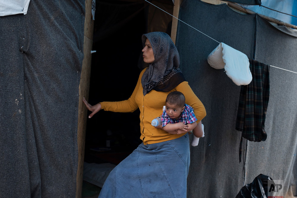 In this Monday, Sept. 19, 2016 photo 30-year-old Rima Al Basir, a Syrian mother from Alepo, enters her makeshift tent carrying her five-month-old baby boy Mohamed Ahmed Bashar at the Ritsona camp north of Athens. Her baby is one of at least seven born in the camp of about 600 since it was set up earlier this year. (AP Photo/Petros Giannakouris)