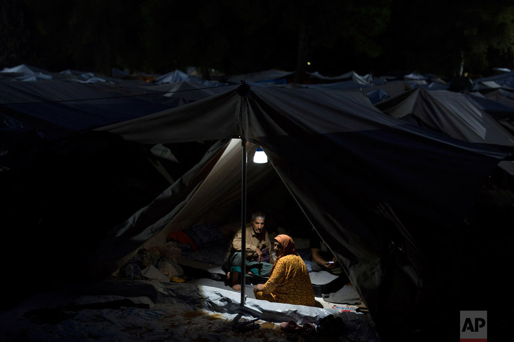 In this Thursday, Sept. 22, 2016 photo, a Syrian couple and visiting friends sit in their tent at the Ritsona camp for refugees and other migrants north of Athens. (AP Photo/Petros Giannakouris)